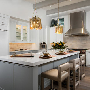 Transitional kitchen remodeling - Inspiration for a transitional dark wood floor and brown floor kitchen remodel in Miami with shaker cabinets, white cabinets, beige backsplash, paneled appliances and an island