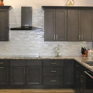 Idéer för ett stort modernt kök, med en undermonterad diskho, skåp i shakerstil, grå skåp, granitbänkskiva, grått stänkskydd, stänkskydd i glaskakel, svarta vitvaror, ljust trägolv och beiget golv