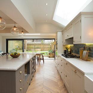 ロンドンの中サイズのトランジショナルスタイルのおしゃれなキッチン (エプロンフロントシンク、シェーカースタイル扉のキャビネット、青いキッチンパネル、サブウェイタイルのキッチンパネル、淡色無垢フローリング、ベージュの床、ベージュのキャビネット、ベージュのキッチンカウンター) の写真