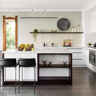 This is an example of a contemporary l-shaped eat-in kitchen in Melbourne with an undermount sink, flat-panel cabinets, white cabinets, beige splashback, white appliances, with island, brown floor and white benchtop.