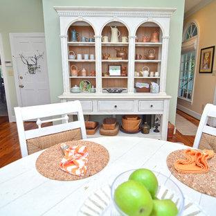 Tropische Küche mit Unterbauwaschbecken, Schrankfronten mit vertiefter Füllung, weißen Schränken, Granit-Arbeitsplatte, Küchenrückwand in Beige, Rückwand aus Steinfliesen, Küchengeräten aus Edelstahl, braunem Holzboden und Kücheninsel in Sonstige