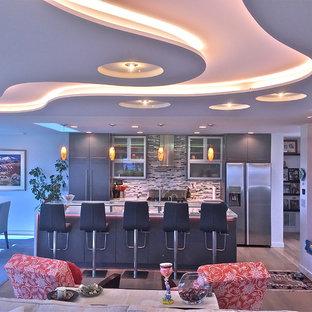 Cette image montre une cuisine ouverte parallèle minimaliste de taille moyenne avec un évier encastré, des portes de placard grises, un plan de travail en verre, une crédence multicolore, un électroménager en acier inoxydable, un sol en bois brun, un îlot central, un placard à porte plane, une crédence en carreau briquette et un sol marron.