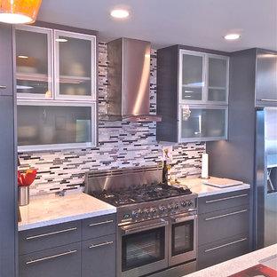 Ejemplo de cocina comedor lineal, moderna, extra grande, con fregadero bajoencimera, armarios tipo vitrina, puertas de armario grises, encimera de vidrio, salpicadero multicolor, salpicadero de azulejos de vidrio, electrodomésticos de acero inoxidable, suelo de madera en tonos medios y una isla