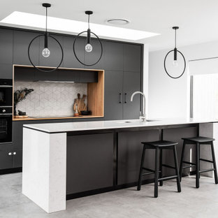 Inspiration for a modern galley kitchen in Hobart with with island, a double-bowl sink, flat-panel cabinets, black cabinets, white splashback, panelled appliances, concrete floors, grey floor and white benchtop.
