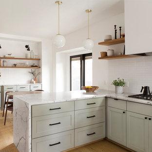 ダラスの北欧スタイルのおしゃれなキッチン (シェーカースタイル扉のキャビネット、グレーのキャビネット、白いキッチンパネル、淡色無垢フローリング、ベージュの床、白いキッチンカウンター) の写真