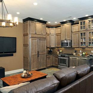 Foto de cocina en L, rural, pequeña, abierta, con armarios con rebordes decorativos, puertas de armario marrones, encimera de granito, electrodomésticos con paneles, suelo de pizarra y península