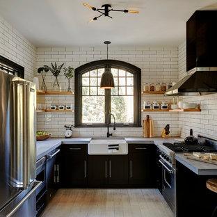 ニューヨークの中サイズのカントリー風おしゃれなキッチン (エプロンフロントシンク、黒いキャビネット、コンクリートカウンター、白いキッチンパネル、サブウェイタイルのキッチンパネル、シルバーの調理設備の、淡色無垢フローリング、アイランドなし、ベージュの床、フラットパネル扉のキャビネット) の写真