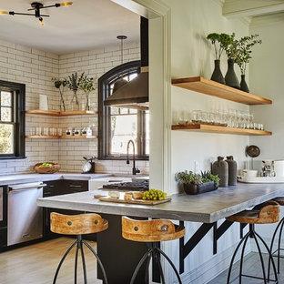 Exempel på ett avskilt, mellanstort industriellt u-kök, med en rustik diskho, svarta skåp, bänkskiva i betong, vitt stänkskydd, stänkskydd i tunnelbanekakel, rostfria vitvaror, ljust trägolv, beiget golv och släta luckor