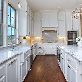 Exempel på ett stort klassiskt vit vitt kök, med en rustik diskho, luckor med upphöjd panel, vita skåp, marmorbänkskiva, grått stänkskydd, stänkskydd i porslinskakel, rostfria vitvaror, mellanmörkt trägolv, en köksö och brunt golv