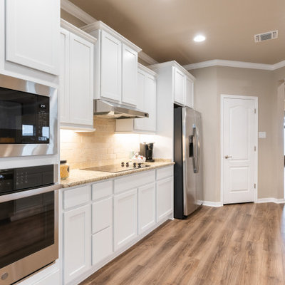 Inspiration for a large craftsman galley open concept kitchen remodel in Austin with an undermount sink, recessed-panel cabinets, white cabinets, granite countertops, beige backsplash, stone tile backsplash, stainless steel appliances, a peninsula and beige countertops