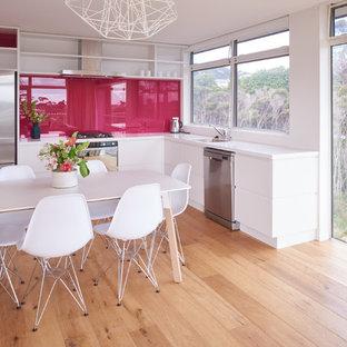 オークランドの小さいコンテンポラリースタイルのおしゃれなキッチン (シングルシンク、フラットパネル扉のキャビネット、白いキャビネット、クオーツストーンカウンター、ピンクのキッチンパネル、ガラス板のキッチンパネル、シルバーの調理設備の、淡色無垢フローリング、アイランドなし) の写真