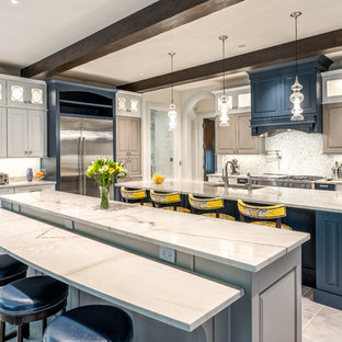 Inspiration for a classic kitchen in Indianapolis with granite worktops, a submerged sink, raised-panel cabinets, blue cabinets, grey splashback, stainless steel appliances, multiple islands, grey floors and white worktops.