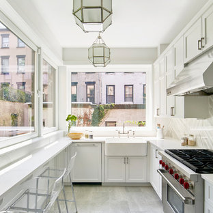 Transitional enclosed kitchen designs - Example of a transitional l-shaped gray floor enclosed kitchen design in New York with a farmhouse sink, shaker cabinets, white cabinets, gray backsplash, stainless steel appliances, no island and white countertops