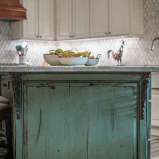 This is an example of a large shabby-chic style l-shaped eat-in kitchen in Houston with a farmhouse sink, raised-panel cabinets, white cabinets, quartz benchtops, white splashback, marble splashback, stainless steel appliances, porcelain floors, with island, brown floor and grey benchtop.