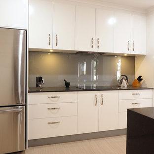 ブリスベンの広いモダンスタイルのおしゃれなキッチン (アンダーカウンターシンク、白いキャビネット、クオーツストーンカウンター、ガラス板のキッチンパネル、シルバーの調理設備、グレーのキッチンパネル、セラミックタイルの床) の写真
