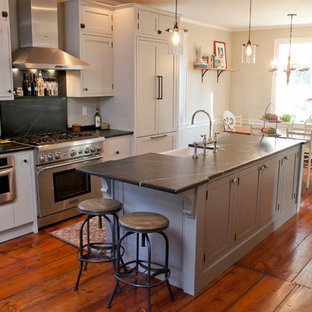 Large farmhouse eat-in kitchen designs - Inspiration for a large cottage galley medium tone wood floor eat-in kitchen remodel in Philadelphia with a farmhouse sink, shaker cabinets, gray cabinets, soapstone countertops, stainless steel appliances and an island