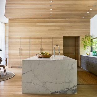 Cette image montre une grande cuisine américaine parallèle design avec un évier encastré, un placard à porte plane, des portes de placard grises, un plan de travail en quartz modifié, un électroménager en acier inoxydable, sol en stratifié, un îlot central, une crédence en fenêtre et un sol marron.