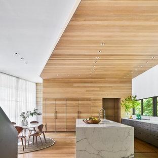 ダラスの広いコンテンポラリースタイルのおしゃれなキッチン (アンダーカウンターシンク、フラットパネル扉のキャビネット、グレーのキャビネット、クオーツストーンカウンター、シルバーの調理設備、ラミネートの床) の写真