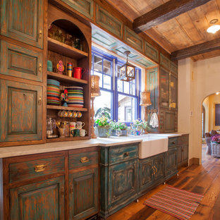 Rustic eat-in kitchen inspiration - Mountain style galley eat-in kitchen photo in Dallas with a farmhouse sink, distressed cabinets, raised-panel cabinets and soapstone countertops