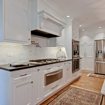 Large elegant u-shaped medium tone wood floor eat-in kitchen photo in Chicago with a double-bowl sink, beaded inset cabinets, white cabinets, quartzite countertops, gray backsplash, stone tile backsplash, stainless steel appliances and an island