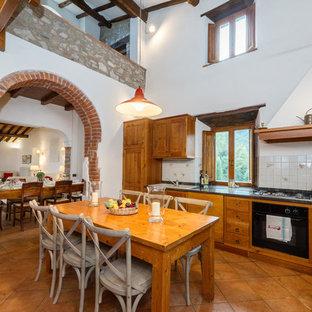 Idee per una cucina in campagna di medie dimensioni con lavello da incasso, ante con bugna sagomata, ante in legno chiaro, top in marmo, paraspruzzi con piastrelle in ceramica, elettrodomestici neri e pavimento in terracotta