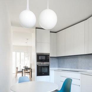 Ispirazione per una cucina abitabile contemporanea con ante lisce, ante bianche e paraspruzzi blu