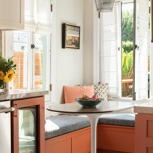 Foto de cocina mediterránea, sin isla, con puertas de armario naranjas y suelo de azulejos de cemento