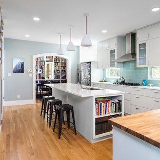 Modern inredning av ett l-kök, med en undermonterad diskho, släta luckor, grönt stänkskydd, rostfria vitvaror, bänkskiva i kvarts, stänkskydd i glaskakel, mellanmörkt trägolv, en köksö och vita skåp