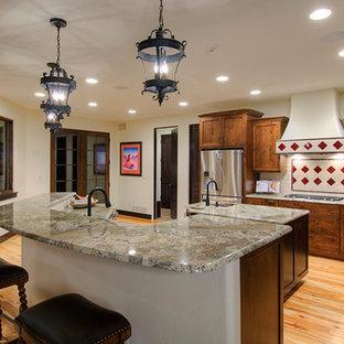 デンバーの大きいサンタフェスタイルのおしゃれなキッチン (シングルシンク、シェーカースタイル扉のキャビネット、濃色木目調キャビネット、御影石カウンター、ベージュキッチンパネル、磁器タイルのキッチンパネル、シルバーの調理設備の、淡色無垢フローリング) の写真