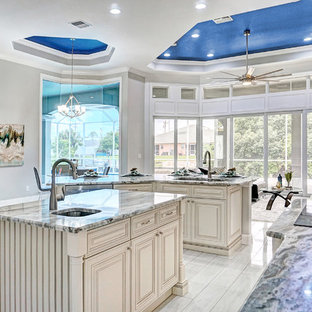 Photo of a mediterranean kitchen in Miami with an undermount sink, raised-panel cabinets, beige cabinets, stainless steel appliances, multiple islands, multi-coloured benchtop and white floor.