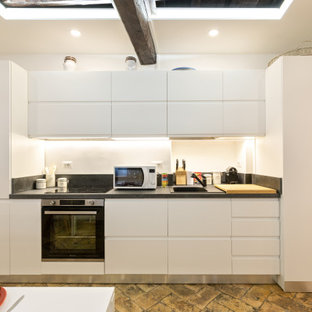 Photo of a small contemporary single-wall eat-in kitchen in Rome with a single-bowl sink, beaded inset cabinets, white cabinets, granite benchtops, grey splashback, granite splashback, black appliances, terra-cotta floors, no island, beige floor and grey benchtop.