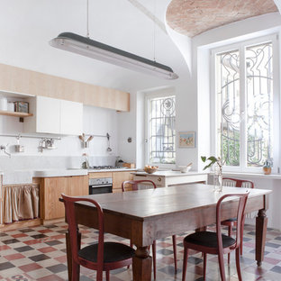 Photo of a large eclectic single-wall eat-in kitchen in Milan with flat-panel cabinets, light wood cabinets, grey splashback, stainless steel appliances, a peninsula and ceramic floors.
