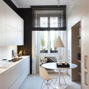 Esempio di una cucina parallela design chiusa e di medie dimensioni con lavello integrato, elettrodomestici in acciaio inossidabile, pavimento in cemento, nessuna isola, pavimento beige, ante lisce, ante bianche e paraspruzzi bianco
