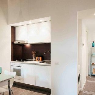 Modelo de cocina lineal, bohemia, pequeña, abierta, con fregadero bajoencimera, armarios con paneles lisos, puertas de armario blancas, electrodomésticos blancos y suelo de madera clara