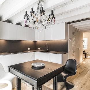 Ispirazione per una cucina minimal di medie dimensioni con lavello sottopiano, ante lisce, ante bianche, paraspruzzi nero, elettrodomestici in acciaio inossidabile, pavimento in legno massello medio, nessuna isola, pavimento marrone e top nero