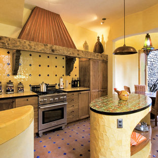 メキシコシティのサンタフェスタイルのおしゃれなダイニングキッチン (シルバーの調理設備、タイルカウンター、落し込みパネル扉のキャビネット、濃色木目調キャビネット、黄色いキッチンパネル、セラミックタイルのキッチンパネル、黄色いキッチンカウンター) の写真