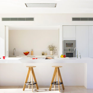 Mid-sized contemporary galley eat-in kitchen in Other with an integrated sink, flat-panel cabinets, white cabinets, solid surface benchtops, white splashback, stainless steel appliances, travertine floors and with island.