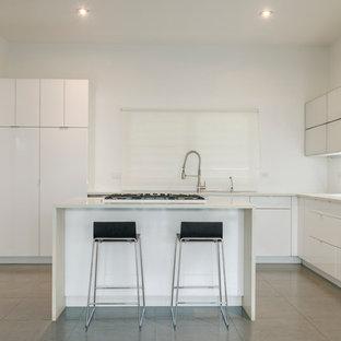 Ejemplo de cocina en U, moderna, pequeña, cerrada, con fregadero bajoencimera, armarios tipo vitrina, puertas de armario blancas, encimera de vidrio reciclado, salpicadero blanco, electrodomésticos blancos, suelo de baldosas de porcelana y una isla