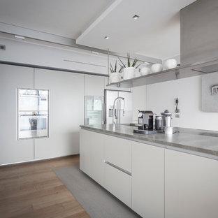 Bild på ett stort funkis kök, med släta luckor, vita skåp, granitbänkskiva, rostfria vitvaror, ljust trägolv och en köksö