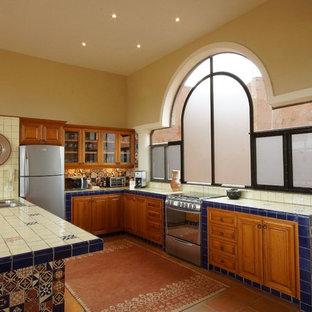 ミネアポリスの中サイズの地中海スタイルのおしゃれなキッチン (ダブルシンク、レイズドパネル扉のキャビネット、中間色木目調キャビネット、タイルカウンター、白いキッチンパネル、サブウェイタイルのキッチンパネル、シルバーの調理設備の、テラコッタタイルの床) の写真