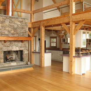 Large rustic open concept kitchen ideas - Example of a large mountain style u-shaped light wood floor open concept kitchen design in Other with glass-front cabinets, white cabinets, solid surface countertops, white backsplash, a peninsula and purple countertops