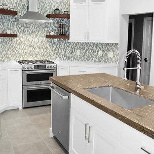 ヒューストンの中サイズのモダンスタイルのおしゃれなキッチン (アンダーカウンターシンク、インセット扉のキャビネット、白いキャビネット、御影石カウンター、マルチカラーのキッチンパネル、ガラス板のキッチンパネル、シルバーの調理設備の、セラミックタイルの床、グレーの床、茶色いキッチンカウンター) の写真