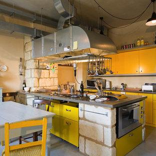 ミラノのインダストリアルスタイルのおしゃれなキッチン (フラットパネル扉のキャビネット、黄色いキャビネット、シルバーの調理設備の、コンクリートの床) の写真