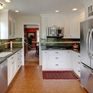 Example of a classic u-shaped enclosed kitchen design in DC Metro with glass-front cabinets, stainless steel appliances, an undermount sink, white cabinets, granite countertops, green backsplash and subway tile backsplash
