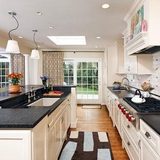 Modelo de cocina de galera, contemporánea, abierta, con fregadero bajoencimera, armarios con paneles empotrados, puertas de armario blancas y salpicadero blanco