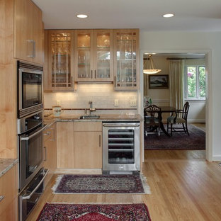 Trendy kitchen photo in DC Metro with glass-front cabinets, stainless steel appliances, an undermount sink, granite countertops, medium tone wood cabinets, white backsplash and subway tile backsplash