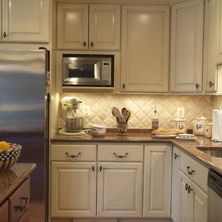 Idées déco pour une cuisine victorienne avec un électroménager en acier inoxydable, un plan de travail en quartz modifié, un évier encastré, un placard avec porte à panneau surélevé, des portes de placard beiges, une crédence beige et une crédence en carrelage de pierre.