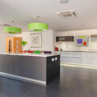 Offene, Große Moderne Küche in L-Form mit Unterbauwaschbecken, flächenbündigen Schrankfronten, weißen Schränken, Quarzit-Arbeitsplatte, Küchenrückwand in Orange, Glasrückwand, weißen Elektrogeräten, Porzellan-Bodenfliesen und Kücheninsel in Essex