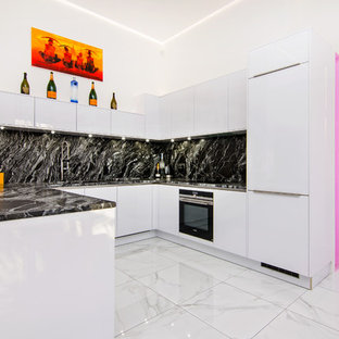Inspiration for a small contemporary u-shaped open plan kitchen in Essex with flat-panel cabinets, white cabinets, granite worktops, black splashback, stone slab splashback, black appliances, porcelain flooring, white floors, black worktops and a breakfast bar.