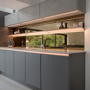Mid-sized modern galley open plan kitchen in Other with an undermount sink, flat-panel cabinets, grey cabinets, quartzite benchtops, black splashback, glass sheet splashback, black appliances, porcelain floors, with island, grey floor and beige benchtop.